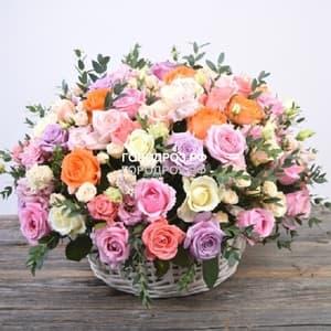 Микс из разных сортов роз с зеленью в корзине